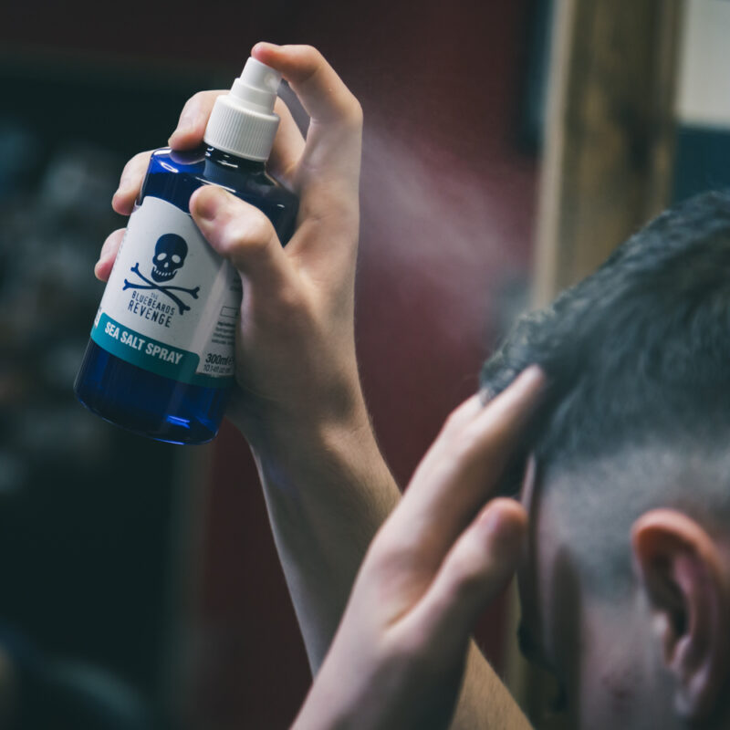 The Bluebeards Revenge vegan friendly sea salt spray being sprayed into a man's hair in a barbershop