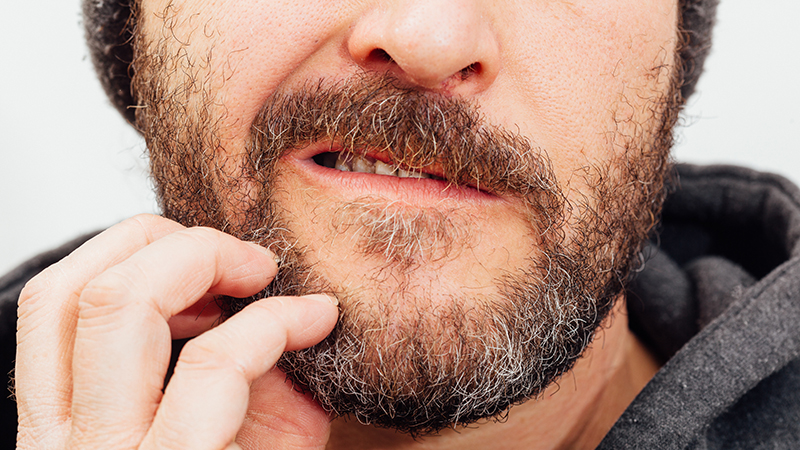 a man itches his beard