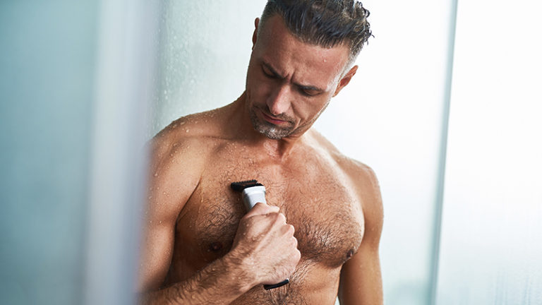a man shaving his chest in the shower