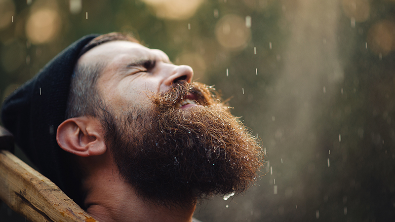 a man gets his beard wet in the rain