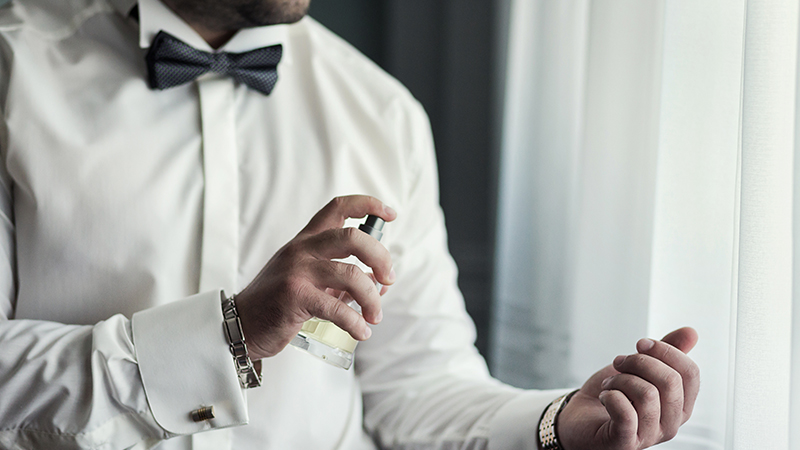 a man applies perfume to himself