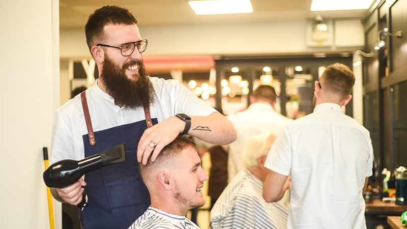 barber ken hermes talks to his client about mental health while styling his hair