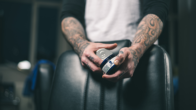 a tattooed barber scoops hair product out of a tub of matt clay by the bluebeards revenge