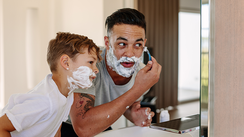 a father and son shaving in the mirror
