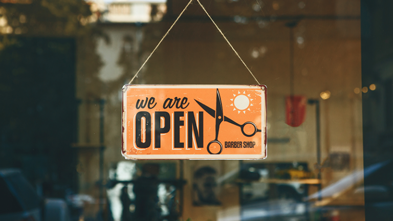 we are open sign hanging on the front of a barbershop