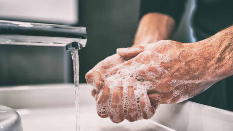 a man washes his hands in warm water and soap