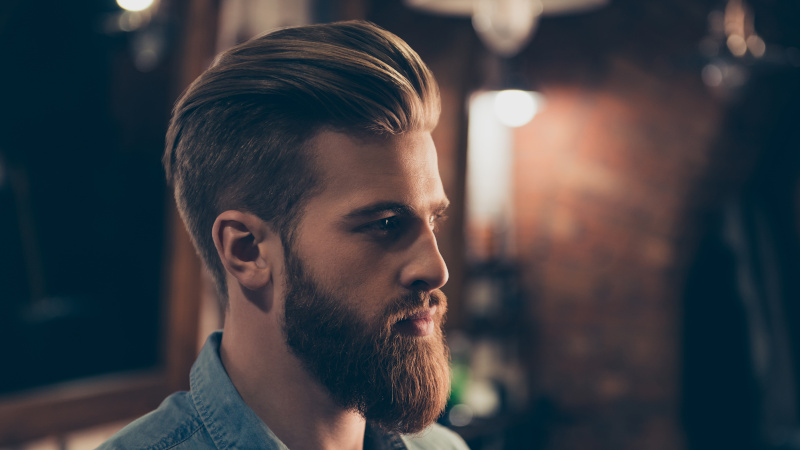 a man with a classic slick back haircut and a beard in the barbershop