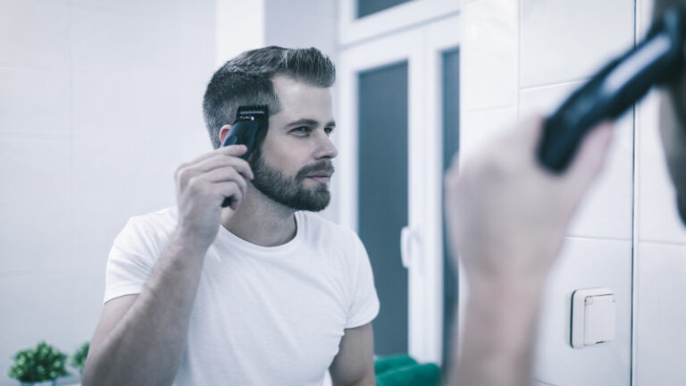 a man cuts his hair in the mirror at home with a pair of clippers