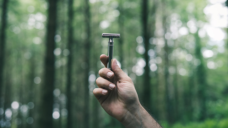 a man holds a plastic free double edge safety razor by the bluebeards revenge in his hand in a forest