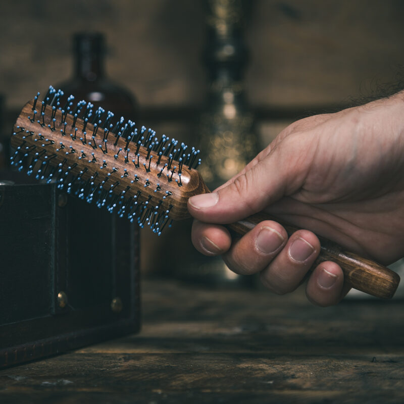 Extra large men's quiff roller by the bluebeards revenge being held in a man's hand