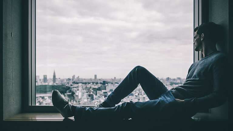 a man sits in the window looking out at a city during lockdown