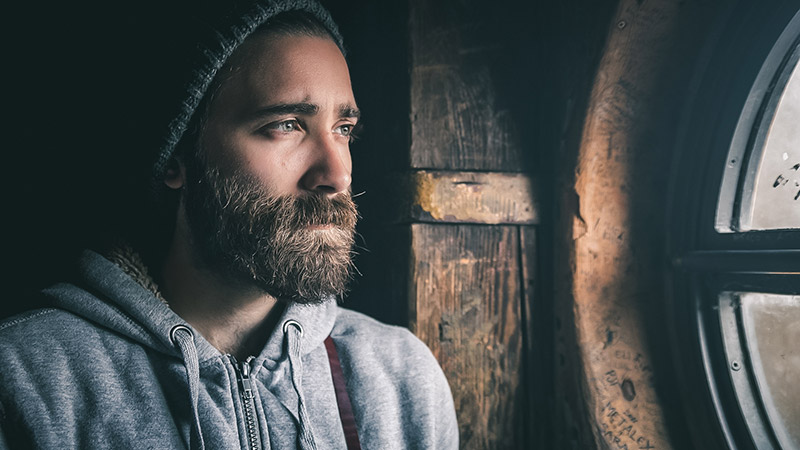 a man with a beard stares through the window during lockdown