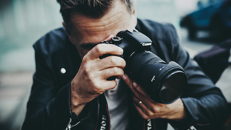 a man taking pictures with a canon camera outdoors