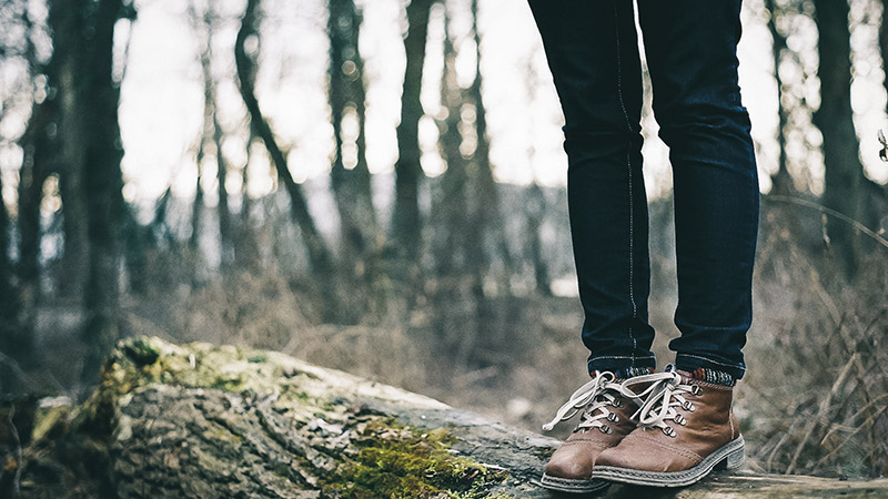 A man stands on a fallen tree in the woods while out walking